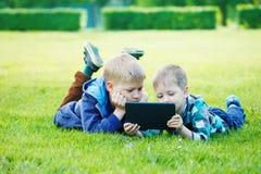 Enfants de mêmes parents à l'aide d'un comprimé Photos stock