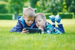 Enfants de mêmes parents à l'aide d'un comprimé, herbe de yingon en parc dans le jour suny Photo stock