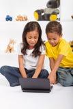 Enfants de mêmes parents à l'aide de l'ordinateur portatif photographie stock