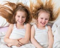 Enfants de mêmes parents adorables se situant ensemble dans le lit Photographie stock libre de droits