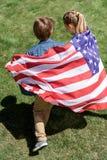 Enfants de mêmes parents adorables tenant le drapeau américain et le fonctionnement dehors Photo libre de droits