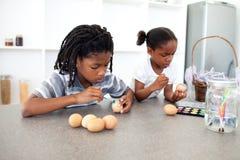 Enfants de mêmes parents afro-américains concentrés peignant des oeufs Photographie stock
