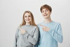 Enfants de mêmes parents amicaux drôles montrant la direction au frère et à la soeur attirants d'invitée de mamans avec les cheve image stock