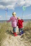 Enfants de mêmes parents avec des filets de pêche marchant sur la plage Image libre de droits