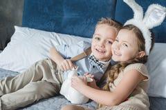 Enfants de mêmes parents avec des lapins de Pâques Images stock