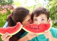 Enfants de mêmes parents avec des tranches de pastèque Photo stock