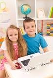 Enfants de mêmes parents avec l'ordinateur portable dans leur chambre photographie stock