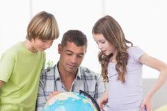 Enfants de mêmes parents avec la carte l'explorant de père sur le globe Photographie stock