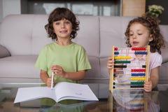Enfants de mêmes parents avec le livre et l'abaque dans le salon Photographie stock