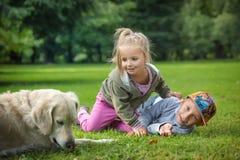 Enfants de mêmes parents avec un golden retriever Photos libres de droits