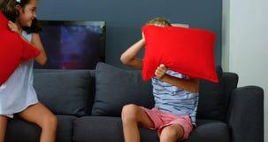 Enfants de mêmes parents ayant le combat d'oreiller dans le salon clips vidéos
