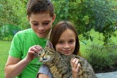 Enfants de mêmes parents caressant avec son chat Image libre de droits