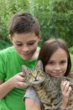 Enfants de mêmes parents caressant avec son chat Images stock