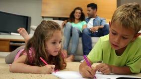 Enfants de mêmes parents colorant sur le plancher tandis que leurs parents s'asseyent sur le sofa banque de vidéos