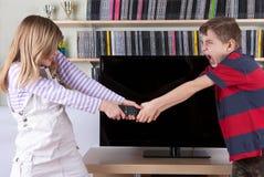 Enfants de mêmes parents combattant au-dessus de l'à télécommande devant la TV Images stock