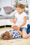 Enfants de mêmes parents combattant dans l'amusement à la maison Images stock