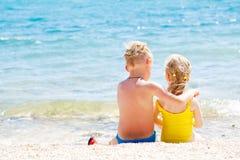Enfants de mêmes parents détendant sur la plage Images stock