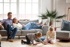 Enfants de mêmes parents d'enfants jouant réunir tandis que relaxin de parents Photographie stock