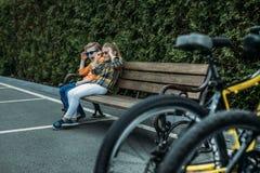 Enfants de mêmes parents dans des lunettes de soleil se reposant sur le banc, bicyclettes se tenant sur le premier plan Photo libre de droits