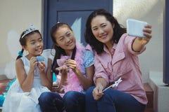 Enfants de mêmes parents dans le costume féerique et la mère prenant un selfie au téléphone portable Images stock