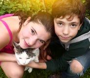 Enfants de mêmes parents de l'adolescence garçon et fille avec le chat Photos stock