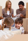 Enfants de mêmes parents de sourire ayant l'amusement pendant déménager de maison Images stock