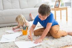 Enfants de mêmes parents de sourire dessinant le mensonge sur l'étage Photo stock