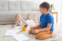 Enfants de mêmes parents de sourire dessinant le mensonge sur l'étage Photos libres de droits