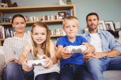 Enfants de mêmes parents de sourire jouant des jeux vidéo avec des parents Photo libre de droits
