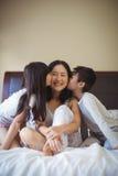 Enfants de mêmes parents embrassant la mère sur des joues dans la salle de lit Image libre de droits