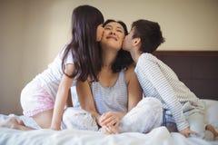 Enfants de mêmes parents embrassant la mère sur des joues dans la salle de lit Photographie stock libre de droits