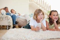 Enfants de mêmes parents ennuyés avec programme de TV Images libres de droits