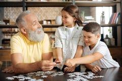 Enfants de mêmes parents et leur grand-père ayant l'amusement tout en faisant le puzzle Images libres de droits