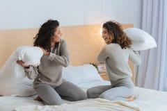 Enfants de mêmes parents extrêmement heureux combattant avec des oreillers à la maison Photographie stock libre de droits