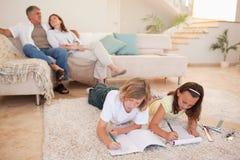 Enfants de mêmes parents faisant le travail sur le plancher avec des parents derrière eux Image libre de droits