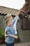 Enfants de mêmes parents frottant le cheval en dehors de l'écurie Images stock
