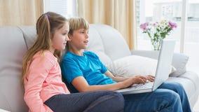 Enfants de mêmes parents heureux à l'aide de l'ordinateur portable sur le sofa photo libre de droits