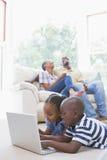 Enfants de mêmes parents heureux à l'aide de leur ordinateur portable Image libre de droits