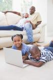 Enfants de mêmes parents heureux à l'aide de leur ordinateur portable Photographie stock