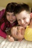 Enfants de mêmes parents heureux à la maison Photos stock