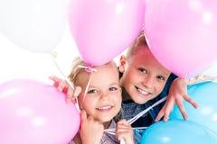 enfants de mêmes parents heureux adorables tenant des ballons et souriant à l'appareil-photo Photos stock