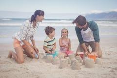 Enfants de mêmes parents heureux avec des parents faisant le château de sable Photo libre de droits