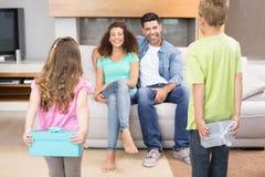 Enfants de mêmes parents heureux cachant des présents derrière leur dos de leurs parents Image stock