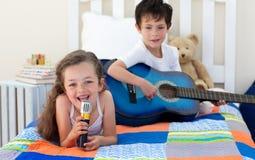 Enfants de mêmes parents heureux chantant et jouant la guitare Photos libres de droits