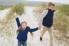 Enfants de mêmes parents heureux courant main dans la main à la plage Images stock