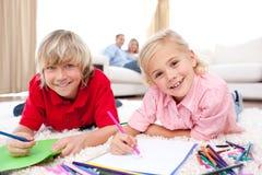 Enfants de mêmes parents heureux dessinant le mensonge sur l'étage Image stock