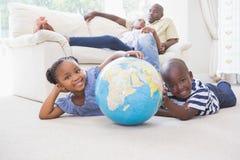 Enfants de mêmes parents heureux employant leur globe photos libres de droits