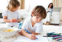 Enfants de mêmes parents heureux mangeant des puces et le dessin Image libre de droits