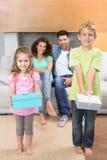 Enfants de mêmes parents heureux montrant des présents devant des parents sur le divan Images stock