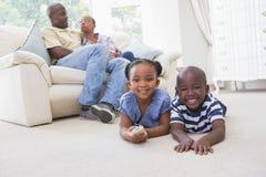 Enfants de mêmes parents heureux s'asseyant à la télévision de observation de plancher Images libres de droits